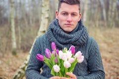 Uomo biondo bello all'aperto con i tulipani Fotografie Stock Libere da Diritti