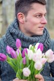 Uomo biondo bello all'aperto con i tulipani Immagini Stock Libere da Diritti