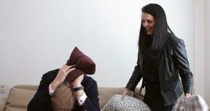 Uomo biondo bello e donna piacevole che hanno guerra in sofà - vittorie del cuscino della moglie stock footage