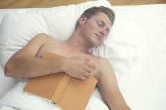 Uomo biondo che dorme a letto e che tiene un libro Fotografia Stock