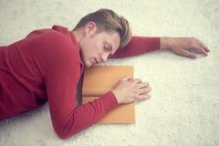 Uomo biondo che dorme sul tappeto e che tiene un libro Fotografie Stock