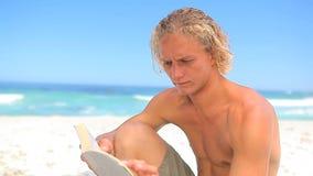 Uomo biondo serio che legge un romanzo video d archivio