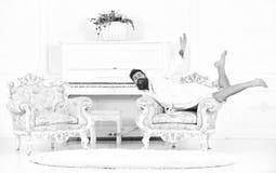 Uomo bizzarro che posa in poltrona Tipo dispari che si trova sulla mobilia antica Milionario nella camera di albergo bianca fotografia stock libera da diritti