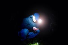 Uomo in blu che dura cercando qualcosa in erba bagnata con luce notte spaventosa o di favola a disposizione, Fotografia Stock