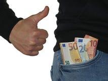 Uomo in blue jeans che mostrano pollice su e le banconote dell'euro, soldi nella tasca isolata su fondo bianco immagini stock libere da diritti