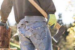 Uomo in blue jeans di lerciume che tagliano legno a pezzi Fotografie Stock