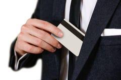 Uomo brillantemente vestito di affari che mette una carta di credito nel suo buttero fotografia stock