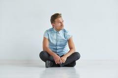 Uomo brutale in una camicia con le brevi maniche che si siedono nella posizione del loto, Fotografia Stock Libera da Diritti
