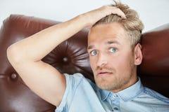 Uomo brutale in una camicia con le brevi maniche che si siedono nella sedia marrone Fotografie Stock Libere da Diritti