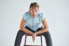Uomo brutale in una camicia con le brevi maniche che si siedono su una sedia rossa Fotografia Stock