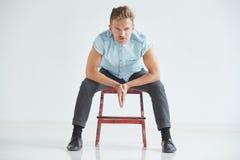 Uomo brutale in una camicia con le brevi maniche che si siedono su una sedia rossa Fotografia Stock Libera da Diritti
