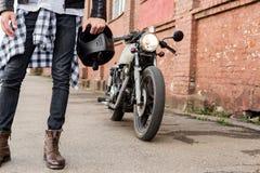 Uomo brutale vicino alla sua motocicletta di abitudine del corridore del caffè fotografie stock libere da diritti