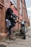 Uomo brutale vicino alla sua motocicletta di abitudine del corridore del caffè immagine stock
