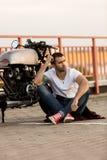 Uomo brutale vicino alla sua motocicletta di abitudine del corridore del caffè Immagine Stock Libera da Diritti