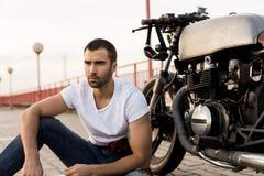 Uomo brutale vicino alla sua motocicletta di abitudine del corridore del caffè fotografia stock