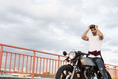 Uomo brutale vicino alla sua motocicletta di abitudine del corridore del caffè immagini stock