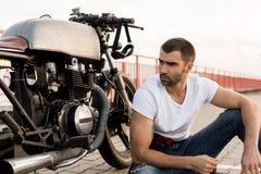 Uomo brutale vicino alla sua motocicletta di abitudine del corridore del caffè fotografia stock libera da diritti