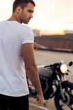 Uomo brutale vicino alla sua motocicletta di abitudine del corridore del caffè Immagini Stock Libere da Diritti
