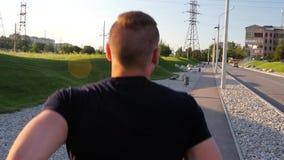 Uomo in buona salute che corre all'aperto nel parco sull'alto video di definizione della strada stock footage
