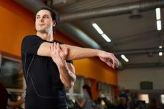 Uomo in buona salute del giovane atleta nello sportwear nero che allunga spalla prima dell'allenamento della palestra Fotografie Stock Libere da Diritti