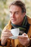 Uomo in caffè esterno con la bevanda calda Immagini Stock