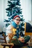 Uomo calmo che si siede davanti all'albero di Natale Immagine Stock