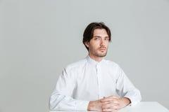 Uomo calmo pensieroso in camicia bianca che si siede alla tavola Fotografia Stock