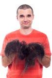 Uomo calvo che tiene i suoi capelli rasi lunghi Fotografie Stock