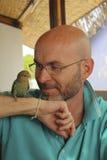 Uomo calvo con una barba con un pappagallo Immagine Stock