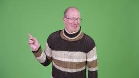 Uomo calvo maturo felice con la dolcevita che ride mentre indicando dito video d archivio