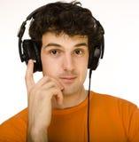 Uomo in camicia arancio con le cuffie che ascolta la musica - isolata su bianco Immagini Stock