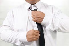 Uomo in camicia bianca che decolla il legame del collo Fotografie Stock Libere da Diritti
