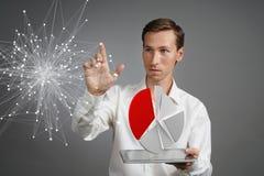 Uomo in camicia bianca che funziona con il diagramma a torta su un computer della compressa, la domanda di pianificazione del bil Immagini Stock