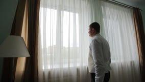Uomo in camicia bianca che lega un legame vicino alla finestra stock footage
