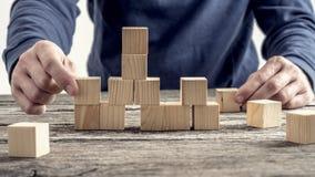 Uomo in camicia blu che sistema i blocchi di legno sulla tavola rustica Immagini Stock Libere da Diritti