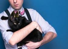 Uomo in camicia, bretella rosa e cravatta a farfalla tenenti gatto nero sveglio in corona dorata brillante su fondo blu con lo sp immagini stock libere da diritti