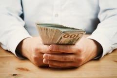 Uomo in camicia che tiene pacco di soldi in sue mani L'economia, risparmio, stipendio, innesto e dona il concetto Fotografia Stock Libera da Diritti