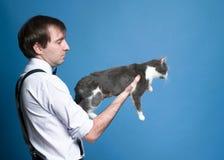Uomo in camicia con le maniche acciambellate che tengono gatto grigio sulle armi stese fotografia stock