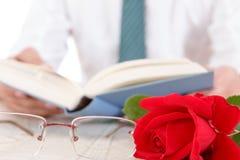 Uomo in camicia e legame con le sue mani che tengono libro aperto e leafin Fotografie Stock Libere da Diritti