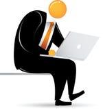 Uomo capo arancione che si siede con il computer portatile Fotografia Stock