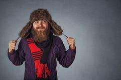 Uomo in cappello di pelliccia, scraf rosso e maglione porpora scuro guardanti per parteggiare fantasticando fotografie stock