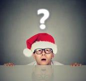 Uomo in cappello di Santa con il punto interrogativo che si domanda circa il regalo Fotografie Stock