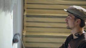 Uomo in cappello e cuffie sul collo, parete della pittura nel colore grigio con un rullo su fondo delle scale di legno video d archivio
