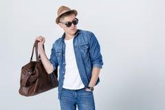 Uomo in cappello ed occhiali da sole che portano borsa di cuoio sulla spalla Immagine Stock
