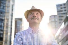 Uomo in cappello ispanico con i baffi che esaminano macchina fotografica che sorride nella città fotografia stock libera da diritti
