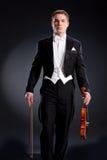 Uomo in cappotto di abito con il violino fotografia stock
