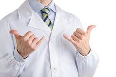 Uomo in cappotto medico che fa gesto di shaka Immagine Stock