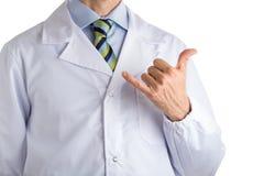 Uomo in cappotto medico che fa gesto di shaka Immagini Stock Libere da Diritti