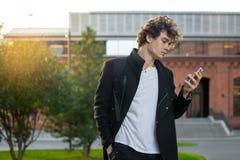 Uomo in cappotto nero che esamina lo schermo del telefono cellulare il fondo urbano di paesaggio urbano immagini stock