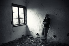 Uomo in casa rovinata Immagine Stock